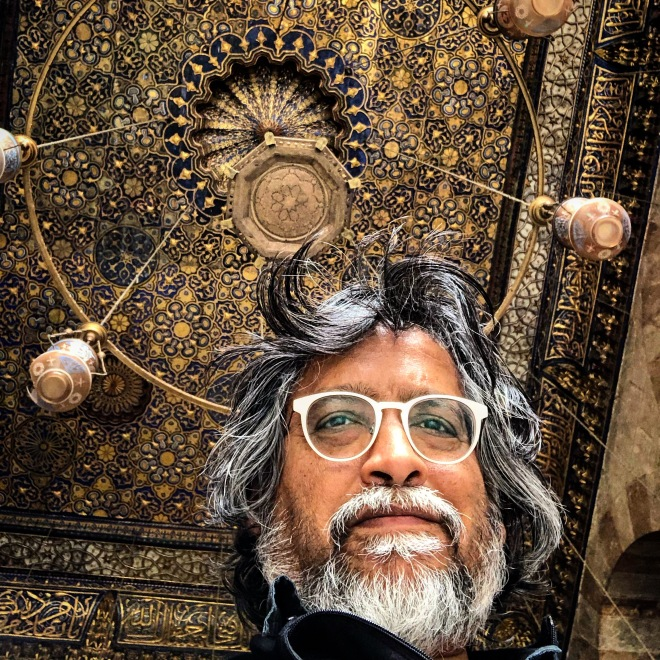 low angle photo of Gavin Barrett framed against ornate ceiling of a medieval Cairo mosque.